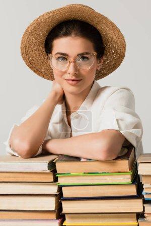 mujer complacida en sombrero de sol y gafas apoyadas en un montón de libros aislados en blanco