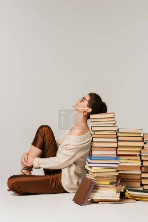 Photo for Side view of young woman in glasses and sweater leaning on stack of books on white - Royalty Free Image