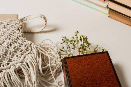 Photo pour Fleurs sauvages en livre avec couverture rigide près de sac bandoulière tricoté sur blanc - image libre de droit