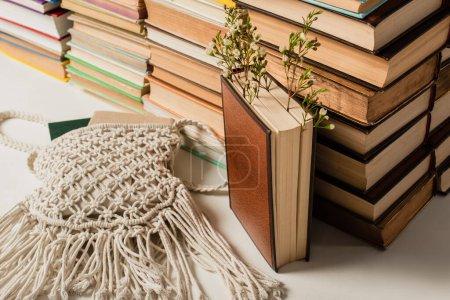 Photo pour Fleurs sauvages près de pile de livres avec couverture rigide et sac bandoulière tricoté sur blanc - image libre de droit