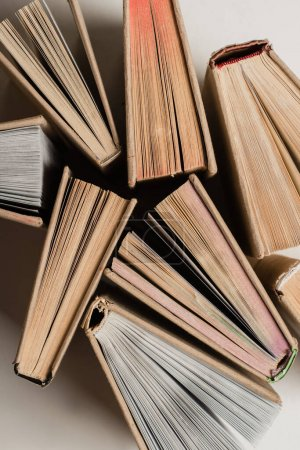 Photo pour Vue de dessus de pile de différents livres en couverture rigide sur blanc - image libre de droit