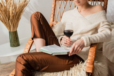 cropped view of young woman sitting in rocking chair with book and glass of wine