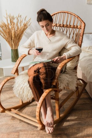 young woman sitting in wicker rocking chair with book and glass of red wine