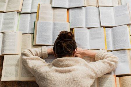 Photo pour Vue de dessus de la femme fatiguée dormant près des livres ouverts - image libre de droit