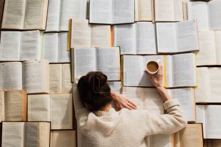 Photo pour Vue du dessus de la femme fatiguée dormant près des livres ouverts avec une tasse de café - image libre de droit