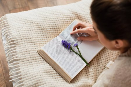 high angle view of blurred young woman reading book with purple flower while resting on bed at home