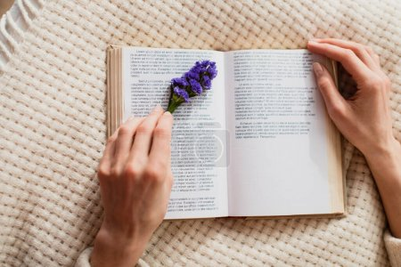 top view of young woman reading book with purple flower