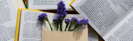 top view of purple flowers in envelope on pile of books, banner