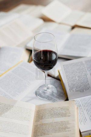 Photo pour Verre de vin rouge sur pile de livres - image libre de droit