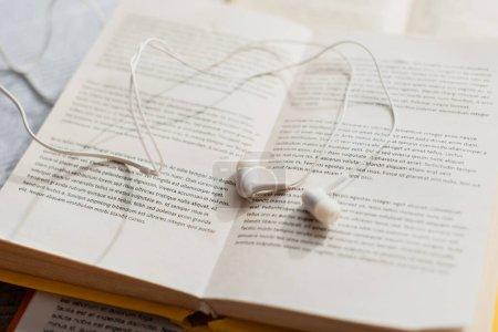Photo pour Gros plan des écouteurs blancs sur les livres flous - image libre de droit