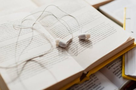 Photo pour Écouteurs blancs sur pile de livres flous - image libre de droit