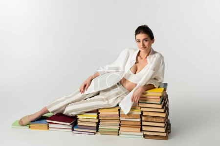 Photo for Full length of brunette young woman in sandals lying on pile of books on white - Royalty Free Image