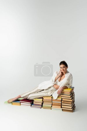 Photo for Full length of pleased woman in sandals lying on pile of books on white - Royalty Free Image