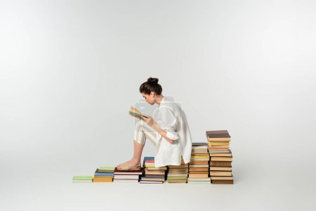 Photo for Side view of young woman in sandals reading while sitting on pile of books on white - Royalty Free Image