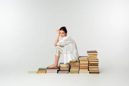 longitud completa de la joven sonriente en sandalias sentadas en un montón de libros en blanco