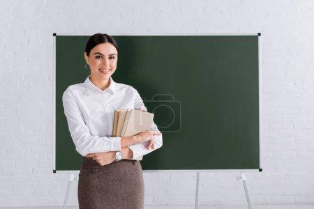 Photo pour Enseignant souriant tenant des livres en classe - image libre de droit