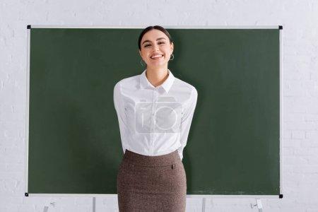 Photo pour Professeur souriant regardant la caméra près du tableau - image libre de droit