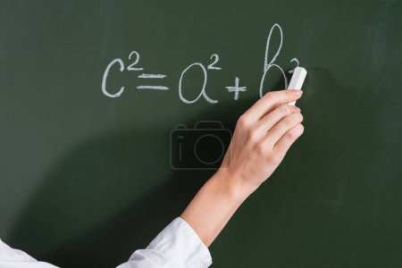 Cropped view of teacher writing equation on chalkboard