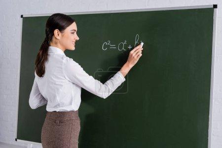 Smiling teacher writing mathematic equation on chalkboard