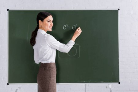 Photo pour Professeur joyeux avec écriture à la craie équation mathématique sur tableau - image libre de droit