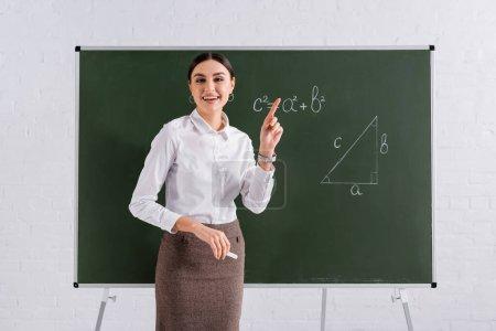 Lächelnder Lehrer zeigt mit Finger auf Kreidetafel mit mathematischer Formel