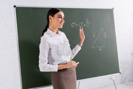 Smiling teacher holding chalk and pointing at equation on chalkboard in classroom
