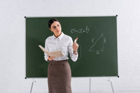 Photo for Teacher with book and chalk pointing with finger during lesson in classroom - Royalty Free Image