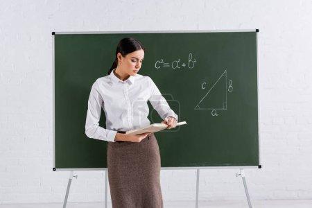 Photo pour Enseignant regardant livre près équation mathématique sur tableau - image libre de droit