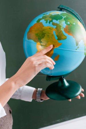 Ausgeschnittene Ansicht des Lehrers, der mit dem Finger auf Globus zeigt