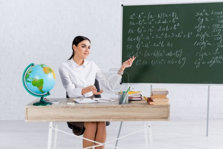Smiling teacher pointing at chalkboard near globe and books in classroom