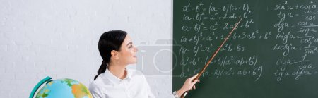 Photo for Smiling teacher pointing at mathematic equations on chalkboard near globe, banner - Royalty Free Image