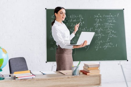 Photo for Teacher pointing at chalkboard while holding laptop during online lesson - Royalty Free Image
