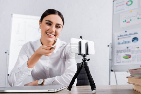 Smartphone on selfie stick near blurred businesswoman pointing with hand during video call