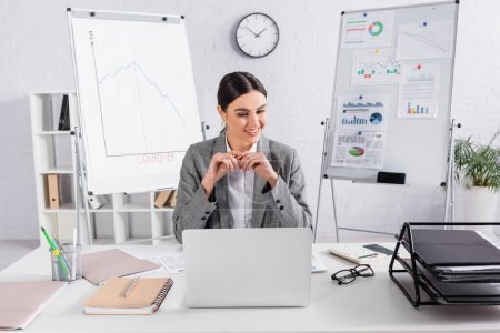 Photo for Cheerful businesswoman looking at calculator near papers and laptop on table - Royalty Free Image