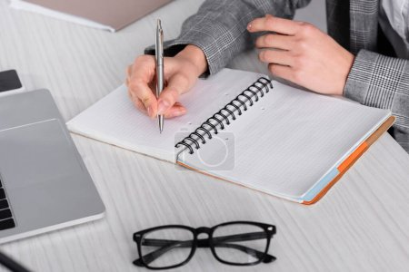 Cropped view of businesswoman writing on notebook near eyeglasses and laptop