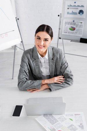 Lächelnde Geschäftsfrau blickt in die Kamera neben Gadgets und Dokumenten