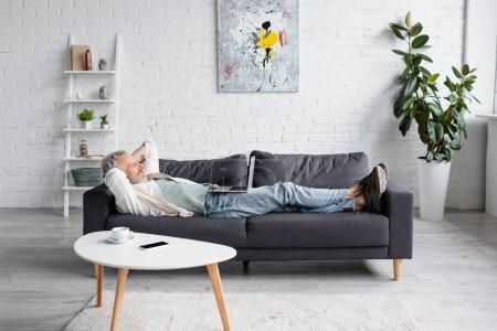 fröhlicher bärtiger Mann, der auf dem Sofa auf den Laptop schaut