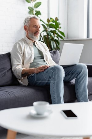 Photo for Bearded man using laptop while sitting on couch near cup of coffee and smartphone with blank screen on blurred foreground - Royalty Free Image