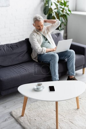 Photo for Cup of coffee and smartphone with blank screen on coffee table near bearded man using laptop on blurred background - Royalty Free Image
