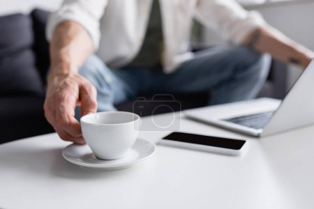 Photo for Cropped view of man reaching cup of coffee table near gadgets - Royalty Free Image