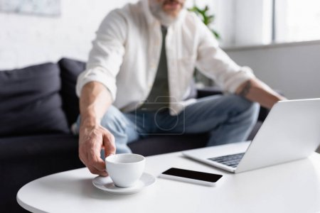 Photo for Cropped view of bearded man reaching cup of coffee table near gadgets - Royalty Free Image