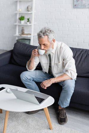 Photo for Bearded man in wireless earphones drinking coffee and looking at laptop - Royalty Free Image