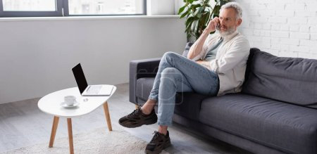 Photo for Bearded man talking on smartphone while sitting on couch near laptop with blank screen, banner - Royalty Free Image