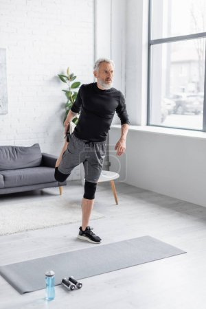 Photo for Full length of bearded and tattooed man in sportswear exercising on fitness mat near dumbbells in living room - Royalty Free Image