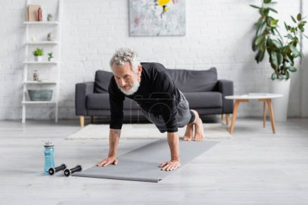Photo for Full length of bearded and tattooed man doing plank on fitness mat near dumbbells in living room - Royalty Free Image
