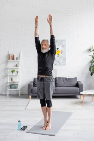 Photo for Full length of bearded and tattooed man exercising on fitness mat near sports bottle and dumbbells in living room - Royalty Free Image