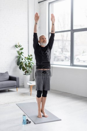 Photo for Full length of bearded and tattooed man exercising on fitness mat near dumbbells in living room - Royalty Free Image