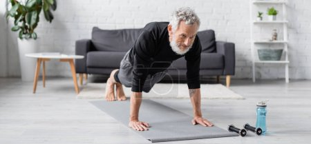 Photo for Bearded and tattooed man doing plank on fitness mat near dumbbells in living room, banner - Royalty Free Image