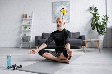 Photo for Man with grey hair meditating on yoga mat near dumbbells in living room, banner - Royalty Free Image