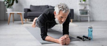 Photo for Bearded man doing plank on fitness mat near dumbbells in living room, banner - Royalty Free Image